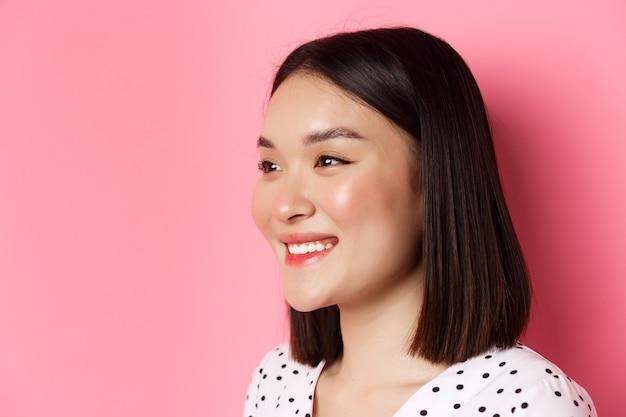 아름 다운 아시아 여자 미소 하 고 찾고 행복 왼쪽, 핑크에 대 한 서의 프로필.