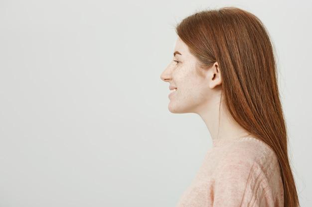 Профиль красивой рыжей женщины с веснушками, смотрящей влево