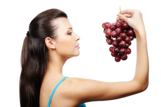 Профиль красивой молодой девушки, держащей гроздь винограда