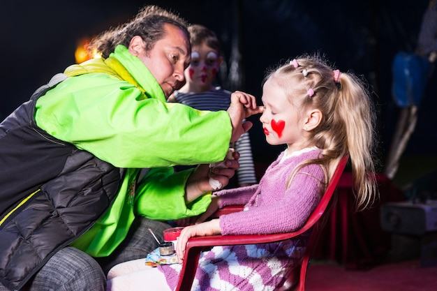 男が顔にピエロメイクをしている椅子に座っているブロンドの女の子のプロフィール
