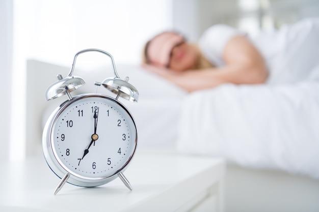 寝床の目覚まし時計を横になっている魅力的な女性のプロフィールは7時に鳴ります