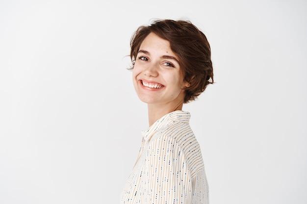 ブラウスの陽気な女の子のプロフィールは頭を回し、幸せそうに見え、あなたに微笑んで、白い壁に立っています