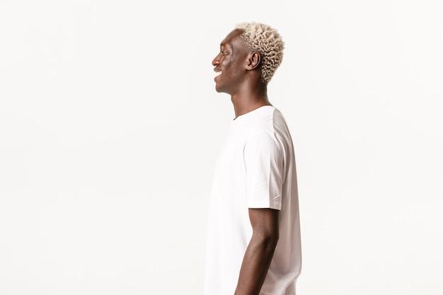 陽気なハンサムなアフリカ系アメリカ人の金髪の男のプロフィール、笑って、左に幸せに笑って、白い壁に立っています。