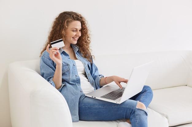 Профиль веселой счастливой молодой женщины с вьющимися волосами, сидя дома, проводя свой выходной день онлайн, собираясь что-то купить, печатая на своем ноутбуке, держа кредитную карту.