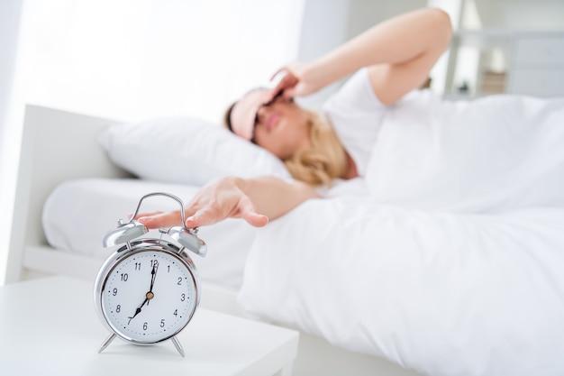 ベッドの目覚まし時計が鳴っている不機嫌な女性のプロフィール