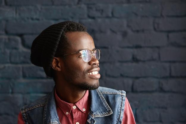 Профиль модного молодого темнокожего мужчины в черной шляпе и джинсовой жилете поверх красной рубашки
