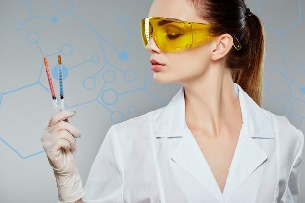 흰색 의료 유니폼, 노란색 보호 안경, 청진기를 착용하고 회색 스튜디오 배경에 두 개의 주사기를 들고 여성 의사의 프로필