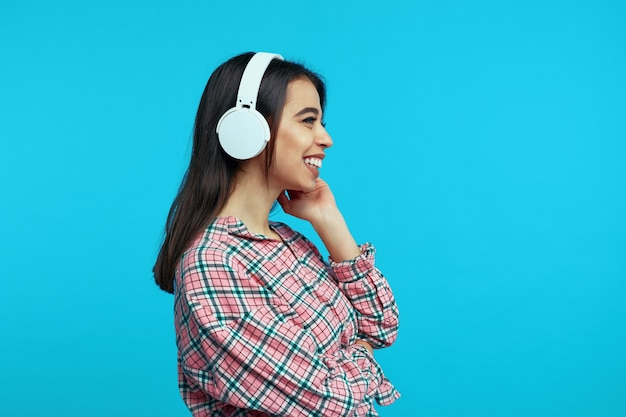 Профиль девушки в белых наушниках, радостно слушает музыку и улыбается
