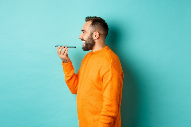 음성 메시지를 녹음하고, 휴대 전화를 들고 스피커폰에 이야기하고, 행복하게 웃고, 청록색 배경에 서있는 잘 생긴 수염 난된 남자의 프로필.