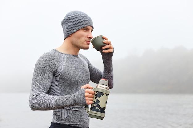 灰色のシャツとキャップを着て熱い飲み物を飲み、遠くを見て、コーヒーを飲む男のプロフィール