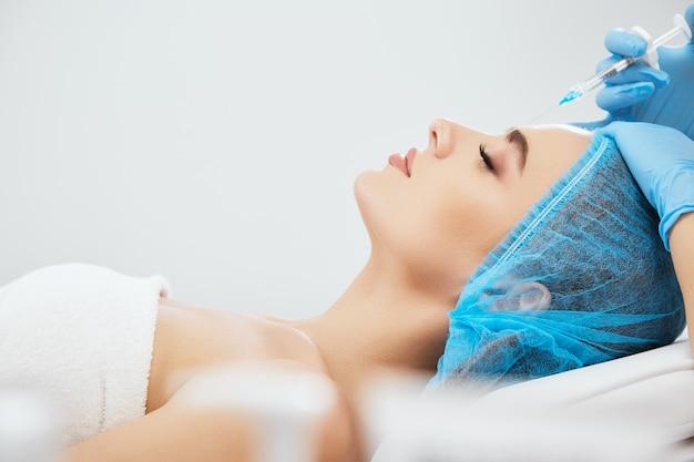 닫힌 된 눈으로 미용 클리닉에서 소파에 누워 파란 모자 모델의 프로필. 필러, 근접 촬영으로 주사기와 윤곽 성형 수술을 하 고 파란색 장갑에 의사의 손
