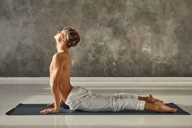 근육질의 젊은 백인 남자가 체육관에서 요가를 연습하고 urdhva mukha shvanasana에서 가슴과 복부를 스트레칭하거나 유연한 척추를 위해 위쪽을 향한 개 포즈를 취하고 눈을 감은 상태로 유지합니다.