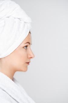 バスタオルで完璧な肌を持つきれいな女性のプロフィール