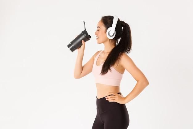 Профиль довольной улыбающейся и симпатичной азиатской девушки в наушниках, у которой перерыв на воду во время тренировки и которая наслаждается продуктивными тренировками под музыку.
