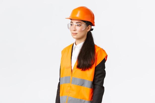 建設エリアを検査し、左を見て、安全ヘルメットと反射服を着て、白い背景に立っている深刻なアジアの女性実業家のプロフィール