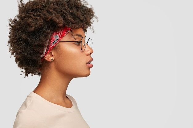 건강한 순수한 피부를 가진 진지한 여성의 프로필은 덥수룩 한 헤어 스타일을 가지고 있습니다.