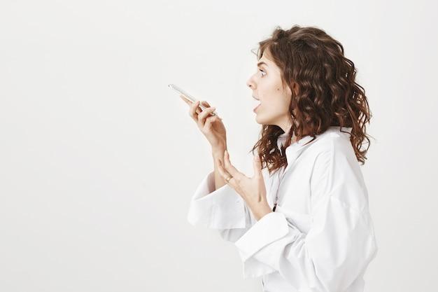 Профиль потрясенной красивой женщины, кричащей на мобильный динамик и записывающей сообщение