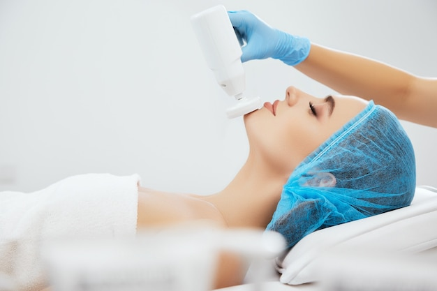 目を閉じて美容クリニックのソファに横たわっている青い帽子の笑顔の女性のプロファイル。ブロサージュ、クローズアップの手順を行う青い手袋の医師の手