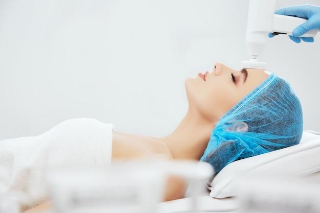 目を閉じて美容クリニックのソファに横たわっている青い帽子の笑顔の女性のプロファイル。ブロサージュの手順を行う青い手袋をはめた医師の手