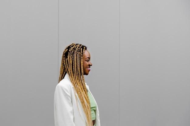 Профиль улыбается молодой афро-американской взрослой женщины с длинными светлыми косами. скопируйте пространство.