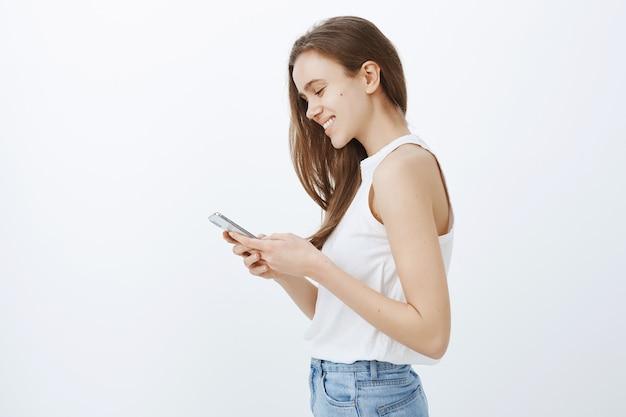 Профиль стильной современной молодой девушки с помощью смартфона и счастливой улыбки