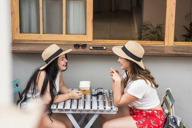 야외 카페에서 여가 시간을 보내는 밀짚모자를 쓴 두 명의 아름다운 여자 친구의 프로필. 레스토랑에서 험담을 하는 두 명의 행복한 아름다운 여성. 카페에서 쾌활한 여성 관광객