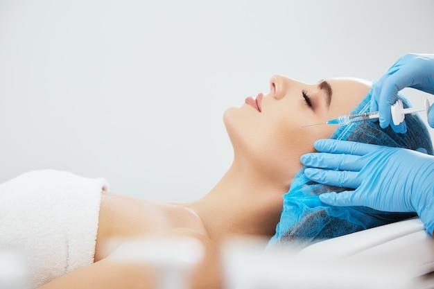 미용 클리닉에서 소파에 누워 파란 모자에있는 여자의 프로필. 필러, 근접 촬영으로 주사기와 윤곽 성형 수술을 하 고 파란색 장갑에 의사의 손