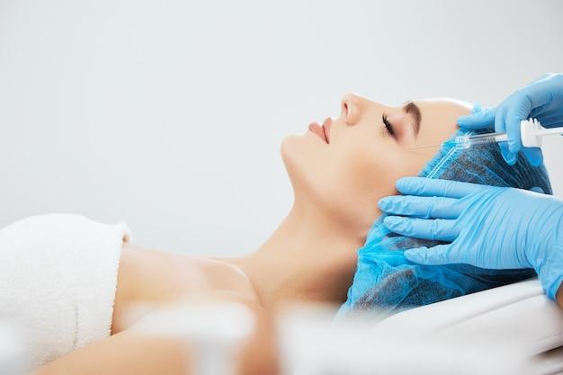 닫힌 된 눈으로 미용 클리닉에서 소파에 누워 파란 모자에있는 여자의 프로필. 필러, 근접 촬영으로 주사기와 윤곽 성형 수술을 하 고 파란색 장갑에 의사의 손