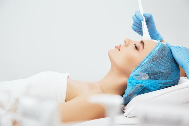 目を閉じて美容クリニックのソファに横たわっている青い帽子の女性のプロフィール。ブラシで彼女の顔に触れる青い手袋の医者の手