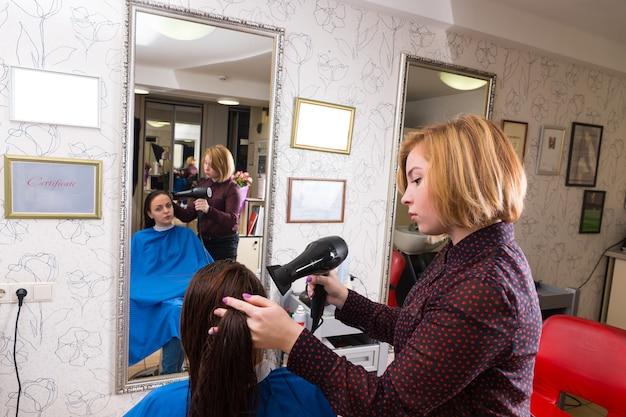 バックグラウンドでミラーの反射とサロンでブロードライヤーを使用して女性ブルネットクライアントの髪を乾燥させる若いブロンドのスタイリストのプロファイル