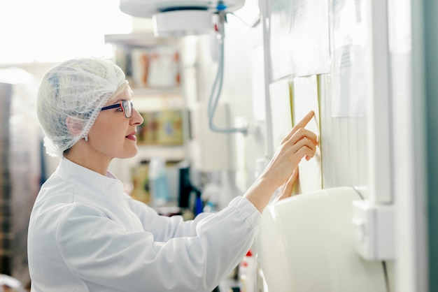 Профиль молодого кавказского белокурого женского графика чтения работника на стене пока стоящ в фабрике еды.