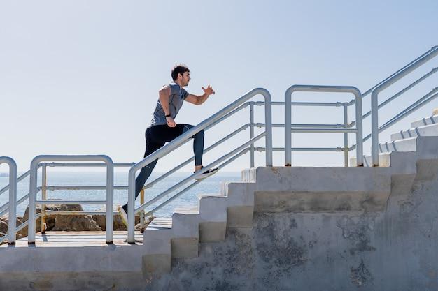 港で澄んだ空と外の2階を走っている若い男のプロフィール
