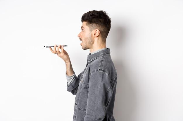 스마트 폰에서 말하는 젊은 남자의 프로필, 음성 번역기 앱으로 번역, 휴대 전화 스피커폰으로 이야기, 흰색 배경에 서.