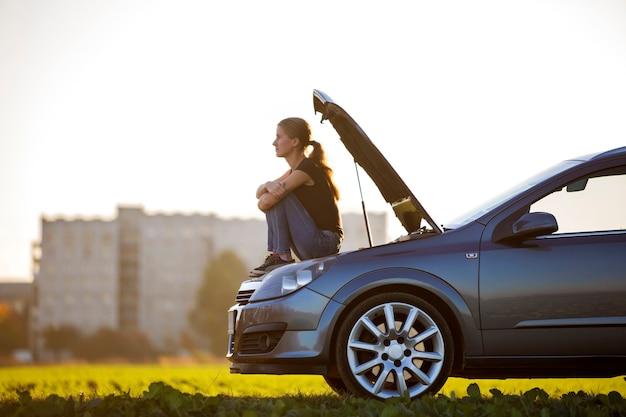 Профиль молодой стройной привлекательной женщины, сидящей на машине с выдвинутым капотом на зеленом лугу, ожидая помощи на фоне копией пространства ясного неба