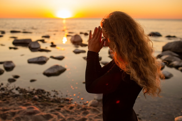 Профиль молодой женщины ослабляя на пляже, размышляя с руками в жесте namaste на заходе солнца или восходе солнца, конец вверх.