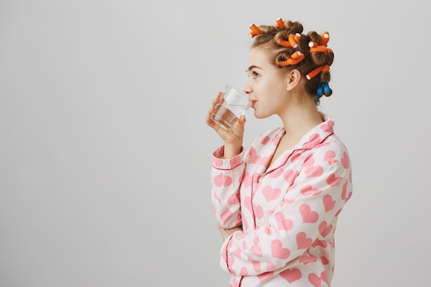 パジャマ姿でヘアカーラー飲料水を持つ若い女性のプロフィール