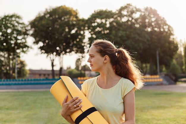 手にマットを保持し、目をそらし、スタジアム、ヘルスケアで運動する準備ができている黄色のtシャツを着ている魅力的な若い女性のプロフィール屋外の肖像画。
