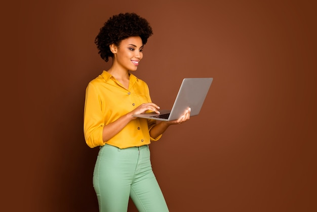 Profile photo of beautiful dark skin wavy lady holding notebook hands searching corporate information writing email wear yellow shirt green trousers isolated brown color