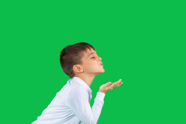 Profile photo the boy on a green isolated background sends an air kiss green isolated background