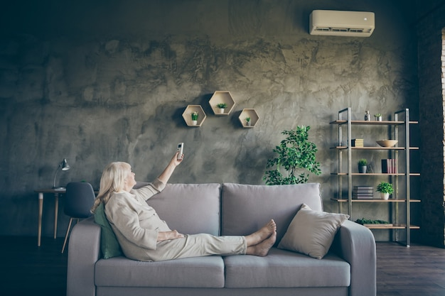 Profile photo of charming white haired aged granny changing conditioner mode turn on hot air sitting sofa divan wear beige pastel clothes living room indoors