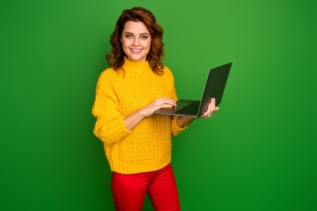 Profile photo of cheerful business lady hold notebook hands browsing freelance it website administrator wear yellow knitted pullover red pants isolated green color wall