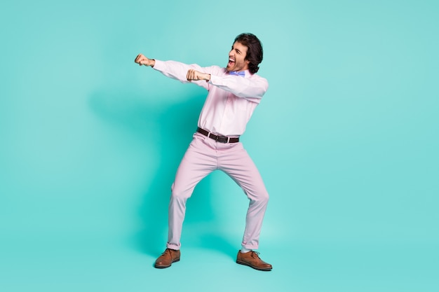 Profile photo of cute brunet wavy hair disco gentlemen dressed pink outfit dancing stretching fists side isolated turquoise color background
