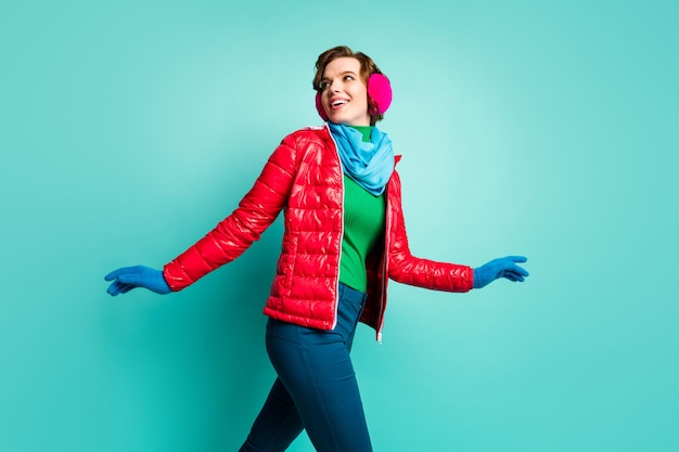 Profile photo of funny lady enjoy winter day active speed skating spend time rejoicing wear stylish casual red overcoat blue scarf pink ear covers trousers isolated teal color wall