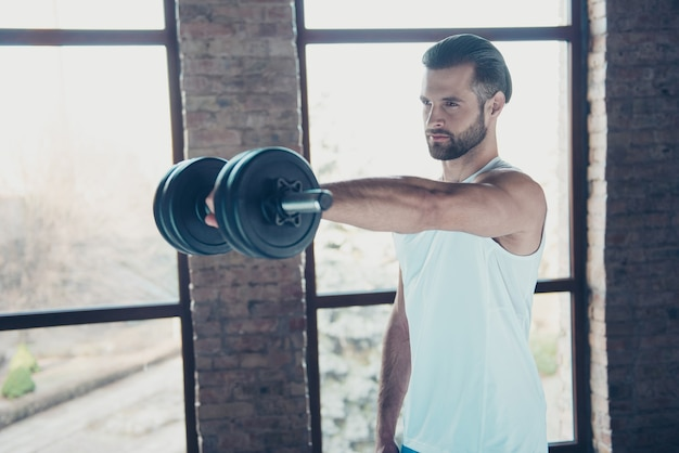 Profile photo of handsome hot beard guy morning training biceps muscles lift heavy dumbbell tempting eyes look sportswear tank-top training house big windows indoors