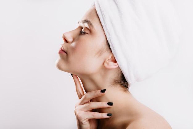 Foto del profilo della signora con un asciugamano bianco sulla testa. donna dopo la doccia senza trucco in posa sulla parete isolata.