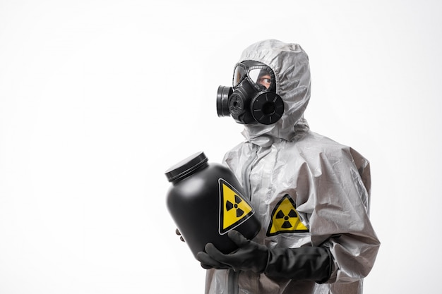 Profile photo: a man in a protective radiation suit and gas mask holds a large black jar with radioactive sign in his hands. biological hazard.