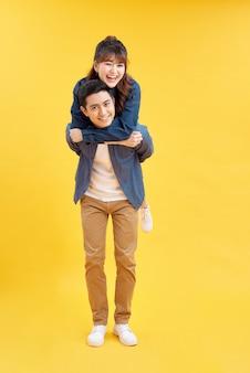 レジャーゲームをしているピギーバックを保持している素晴らしい男と女のプロフィール写真は、カジュアルなジーンズの服を着て、灰色の背景を分離しました
