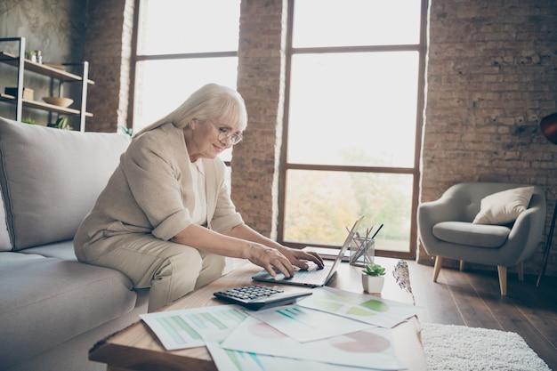 ノートブックを使用して驚くべき白い髪の老いたおばあちゃんのプロフィール写真入力メール入力回答同僚パートナー座って快適ソファソファリビングルームオフィススタイル屋内