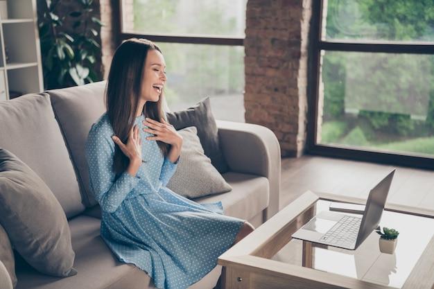 아름다운 쾌활한 여성의 프로필 사진은 스카이프 노트북 온라인 화상 통화 날짜 남자 친구 회의에서 검역을 보내고 집에 앉아 소파에 세련된 점선 드레스를 입고 실내에서 이야기합니다.