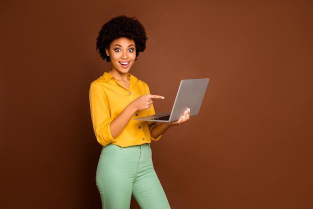 좋은 소식 제공을 보여주는 손가락 화면을 나타내는 노트북을 들고 아름 다운 어두운 피부 비즈니스 아가씨의 프로필 사진 노란색 셔츠 녹색 바지 절연 갈색 색상